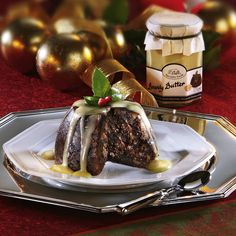 A rich Christmas pudding looks extra-decadent teamed with chocolate Cymbidium orchids. Luscious flowers online. Florist. Flower Delivery